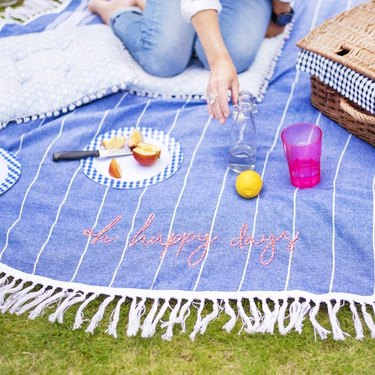 embroidered blue and white picnic blanket with person and food