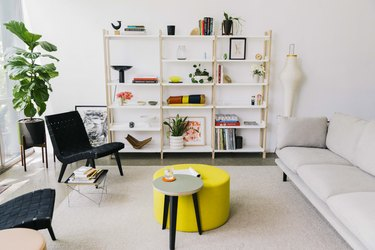 bright living room with yellow coffee table, white shelving, and seating