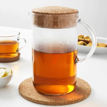 pitcher with amber liquid near cup and food in the background