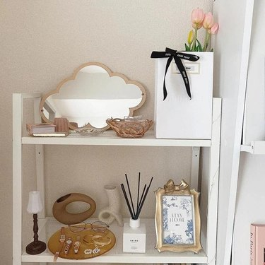 shelf with various trinkets including a cloud shaped mirror