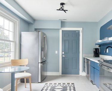 Blue kitchen with stainless refrigerator, stove.