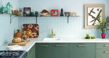 Kitchen with green cabinets, white backsplash, open shelf.