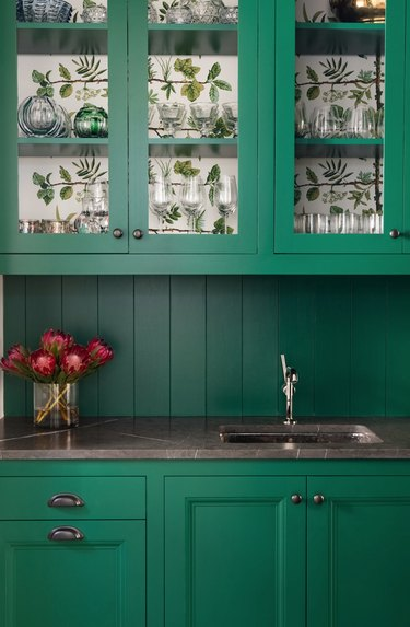 Green kitchen cabinets with wallpaper inside.