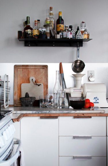 White kitchen with black shelf for bar supplies hanging above counter.