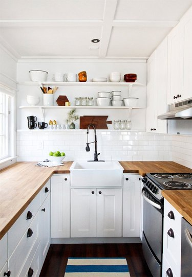 White kitchen with black floors, subway tile.