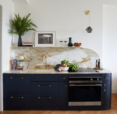 Art deco kitchen with navy cabinets, marble counter and backsplash, plant, art.