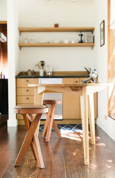 Small kitchen with dining table and wood cabinets.