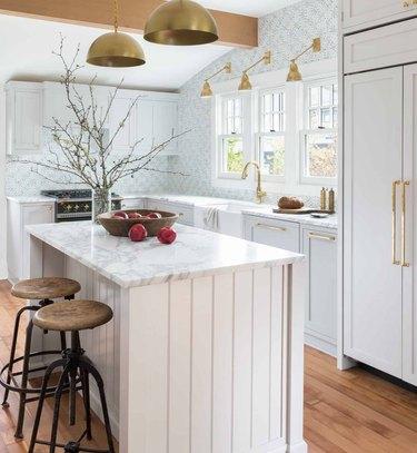 Modern farmhouse kitchen with island, marble, brass pendants, sconces, wood floor.