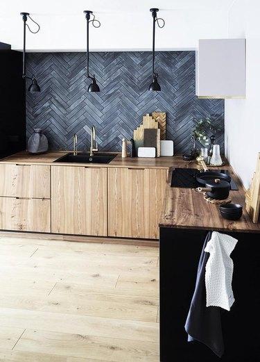 Kitchen with black tile backsplash, wood cabinets.