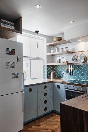 Kitchen with blue cabinets and backsplash, open shelves.