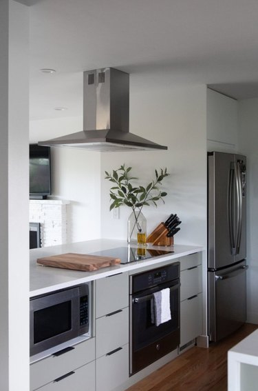 Small kitchen with microwave under counter, stainless hood.