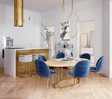 Kitchen with gold hood, gold bar, dining area, chandelier, blue velvet chairs.