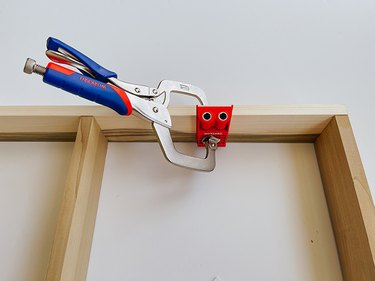 Clamp the pocket hole jig to the wooden base.