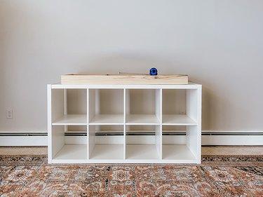 Center the wooden base on the bottom of the IKEA Kallax shelf.