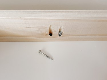 Detail of the screws going through the pocket holes into the bottom of the Kallax shelf.
