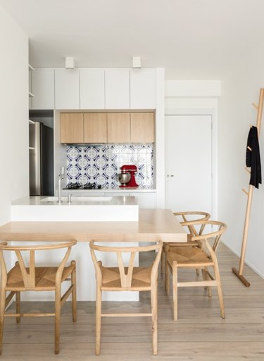 Small kitchen with dining counter, tile backsplash, modern wood chairs.