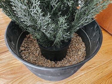 Set the plant on top of the pea gravel in the pot.