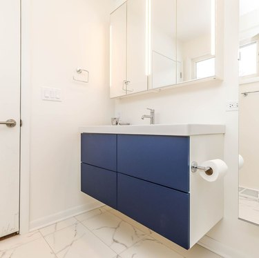 bathroom space with vanity with blue fronts