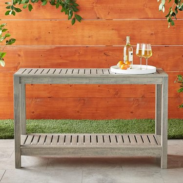 outdoor gray console table with wine bottle and glasses