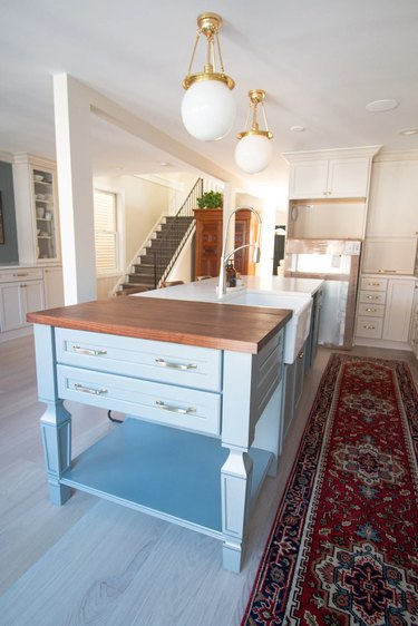 blue butcher block at end of white island in modern kitchen