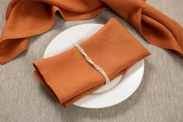terra cotta linen napkins near white plate