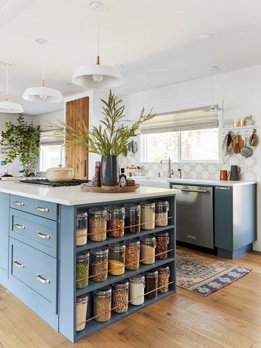 blue kitchen island with glass canisters stored at end