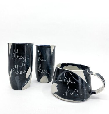 """black and white mugs with writing that says """"they them"""" and """"he him"""" and """"she her"""""""
