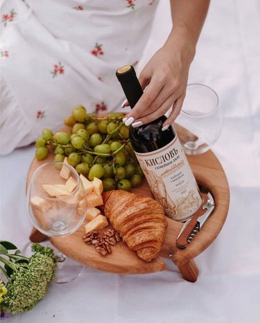 overhead view of person placing wine bottle in serving tray with bread and fruit