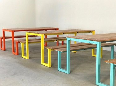 three outdoor tables with legs in red-orange, yellow, and teal colors