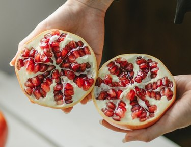 person holding pomegranate halves with seeds