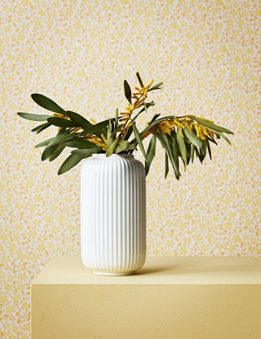 white fluted vase with plant on yellow table with yellow patterned wall in the background