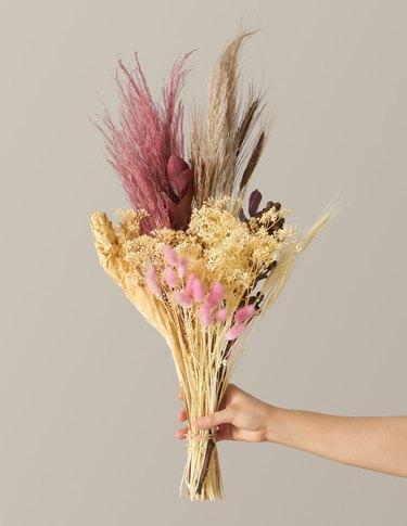 person holding dried floral arrangement
