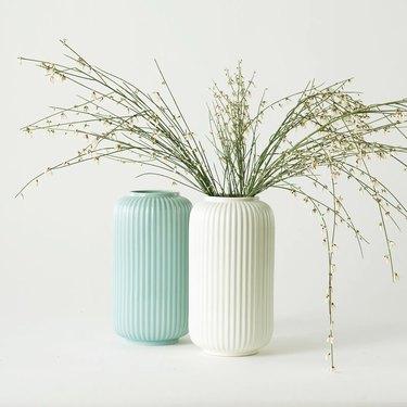 light blue vase and white vase, white vase has dried florals
