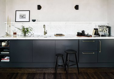 kitchen with marble backsplash and matching countertop with shelf