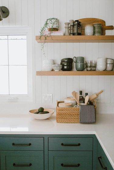 Kitchen with white shiplap backsplash, open shelves, green cabinets.