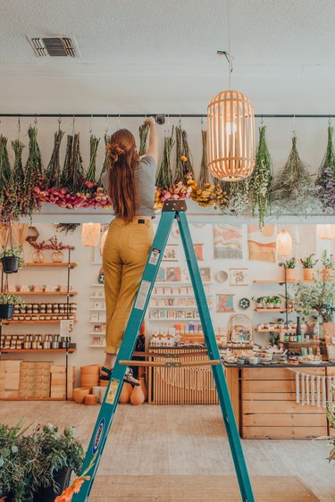 person hanging flowers in a shop
