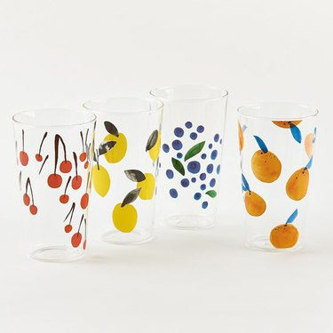 four glass tumblers in various fruit patterns