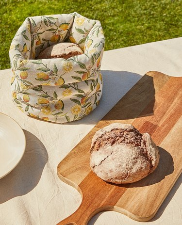 lemon patterned break basket near cutting board with bread
