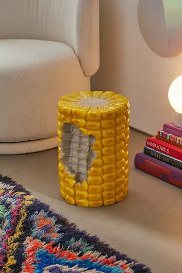 corn shaped stool near couch and lamp with books