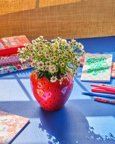flowers in strawberry shaped vase on table near writing tools