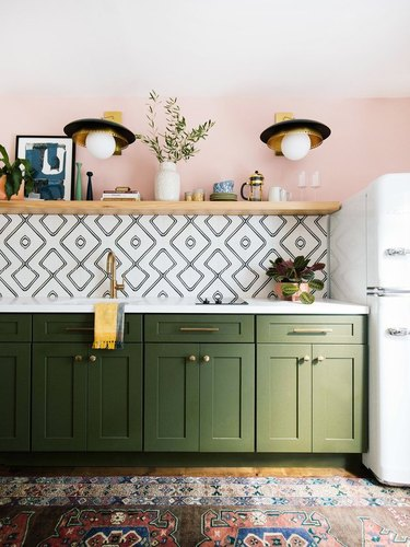 Maximalist kitchen with pink walls, tile and green cabinets