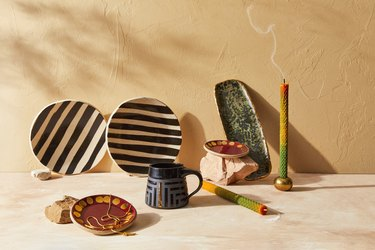 home goods near light wall including striped dishes and mug and candle stick