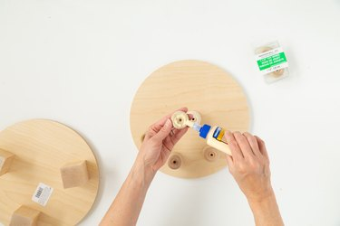 Add glue to wood circle for DIY plant riser