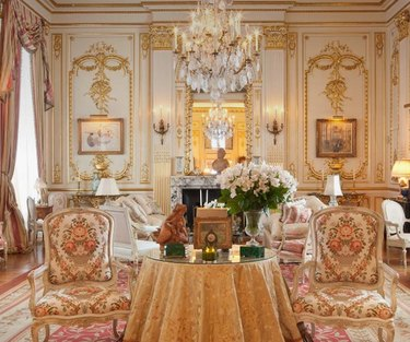 room with gold trim and chandelier and ornate chairs near table