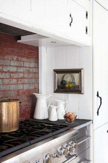 white kitchen with slate countertops and brick backsplash