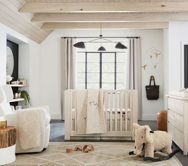 nursery space with light walls and crib and black lighting fixture