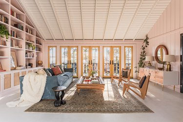 A-frame living room with built-in bookcases, pink walls, earthy furniture, yellow French doors, and eclectic decor.