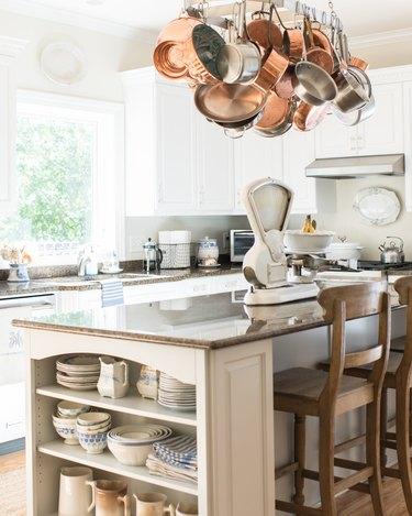 vintage servingware displayed on shelf at end of kitchen island