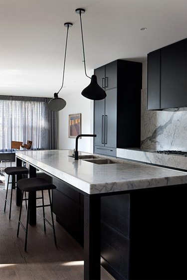 black monochromatic kitchen with marble countertops