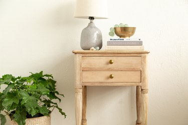 Bleach wood side table next to plant, with a lamp and books